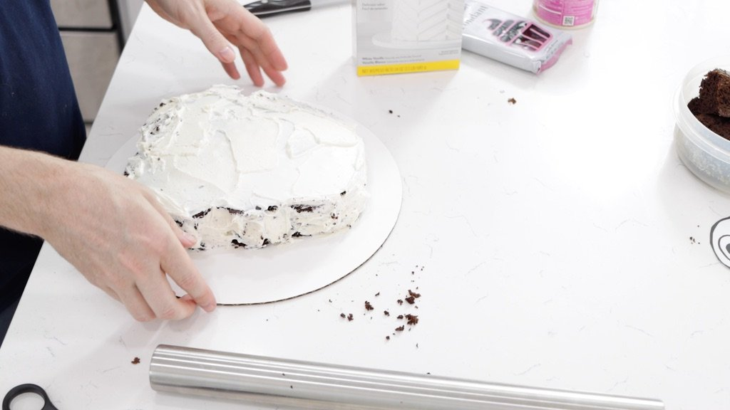 Frosted chocolate cake on a white cake board.
