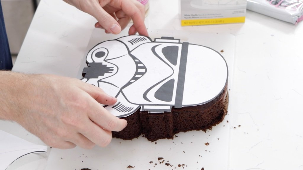 Stormtrooper stencil on top of a trimmed chocolate cake