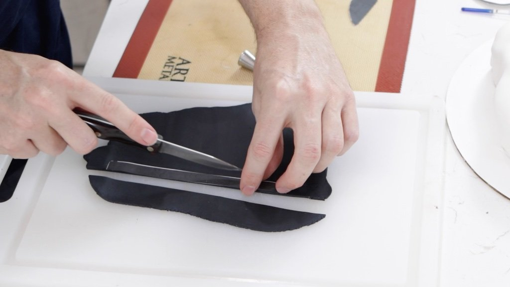 Hand cutting black fondant with a knife