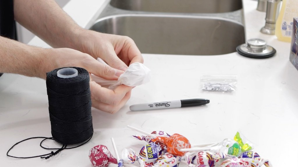 Hand wrapping tissue paper around a blow pop